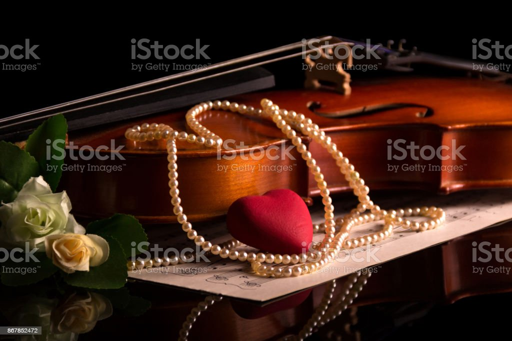 Violin, music notes and a pearl necklace isolated on black stock photo