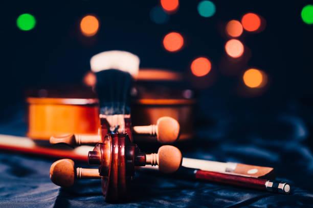 geige auf bunten bokeh hintergrund - philharmonie stock-fotos und bilder