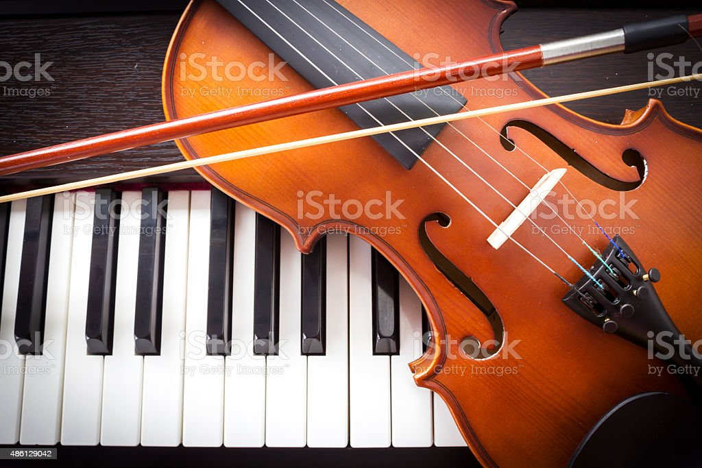 Violin on piano keyboard. stock photo