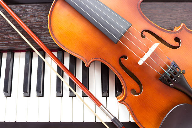 Violin on piano keyboard. Violin and piano keyboard. Music background. Top view. string instrument stock pictures, royalty-free photos & images