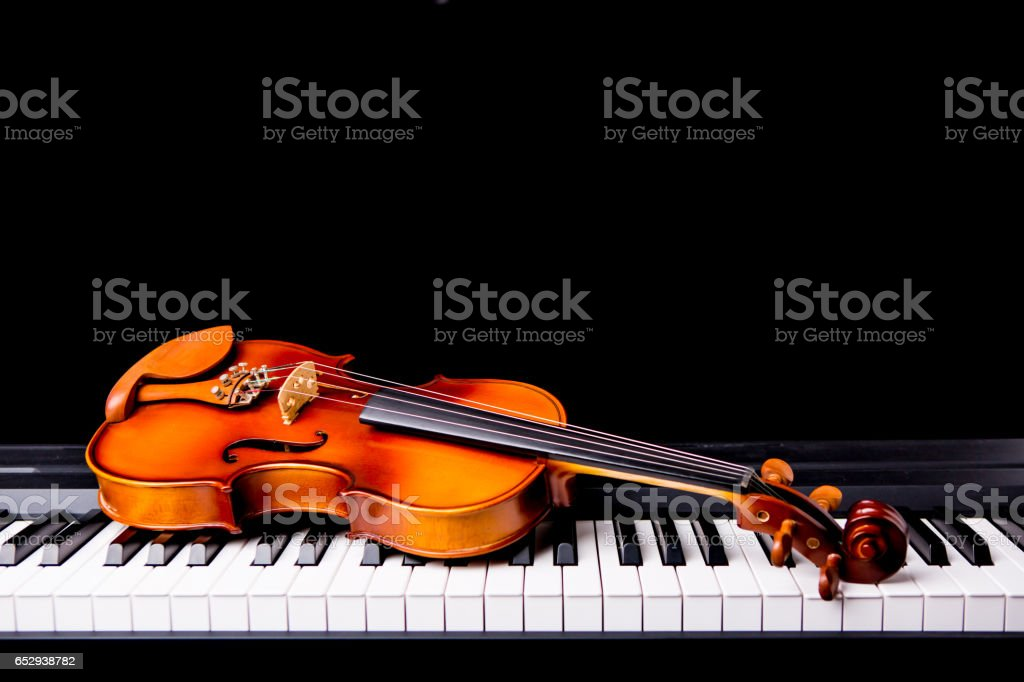 Violin on the piano on a black background stock photo