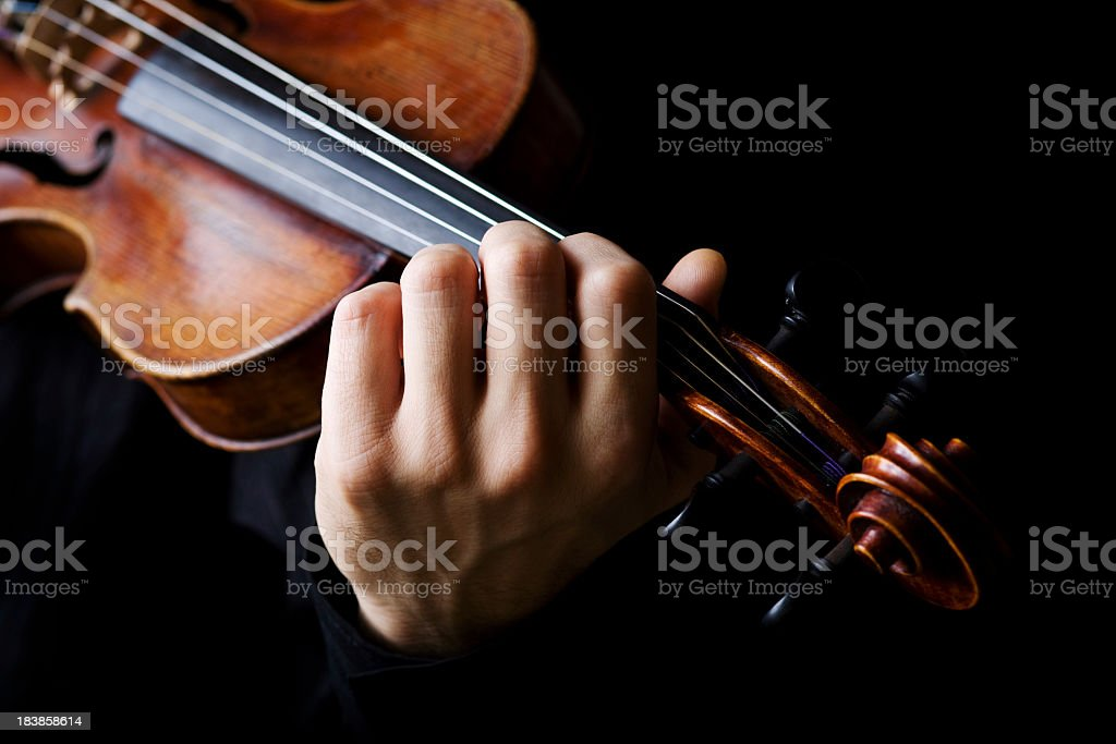 Violin player on a black background stock photo