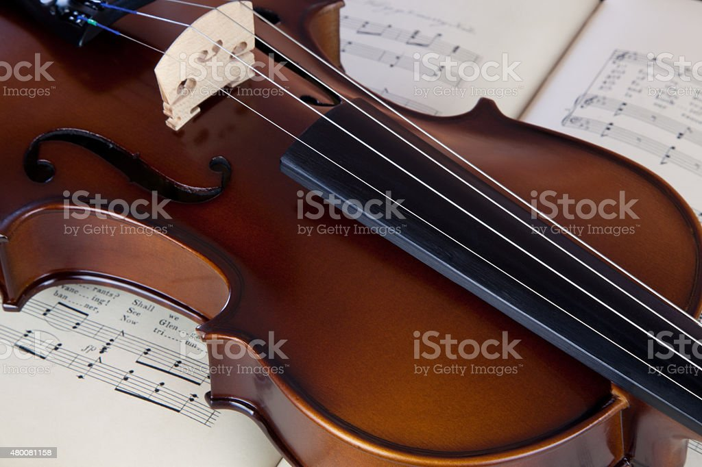 Violin resting on open sheet music book stock photo