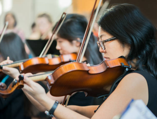 Violin Section of All Ages Community Orchestra Performing in Concert stock photo