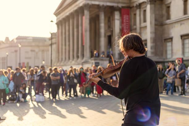 Artista callejera violín tocando para el público - foto de stock