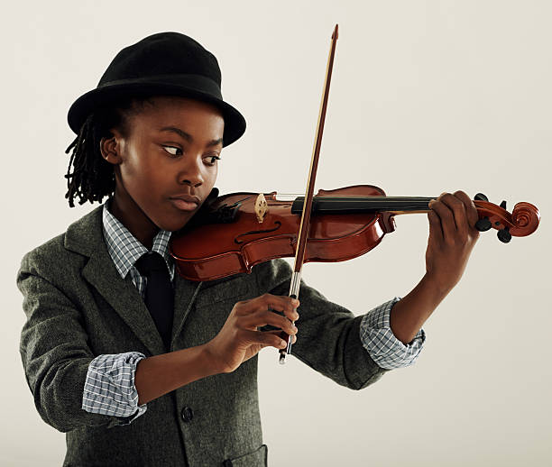 Violin virtuoso A young African-American boy playing a violin child prodigy stock pictures, royalty-free photos & images