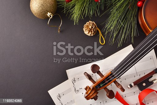 Violin with bow and sheet music with Christmas decoration on black background. Christmas festive gift and concert concept. Top view. Horizontal composition.