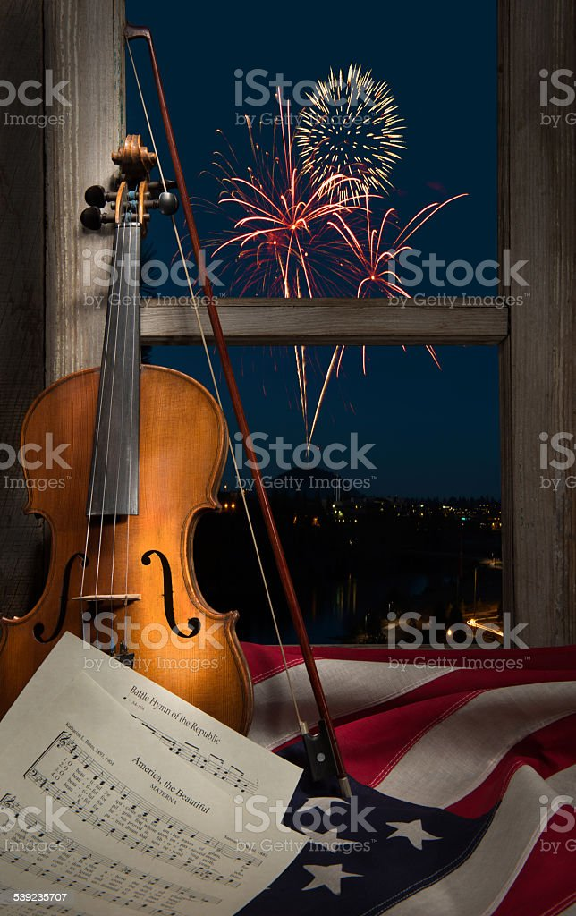 Violin with sheet music,fireworks and the American flag stock photo