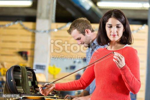 Mid adult woman is violinist, shopping in local instrument repair shop. Musician is checking bow strings while dropping violin off to be repaired by small business owner. Employee is repairing instruments in the background.