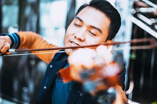 Musician, Art, Passion, Hobby - Passionate young violinist street performing his art to the public. Practicing his craft.