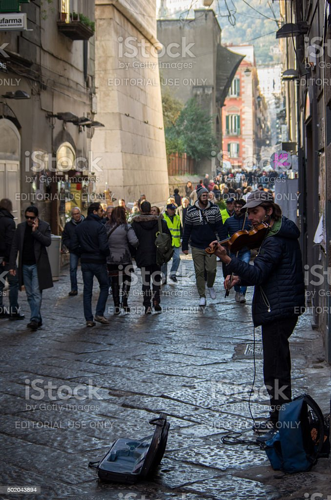 Violinist is playing in Naples while tourists are walking stock photo