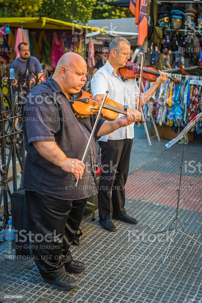 Violinist musician buskers performing in El Rastro market Madrid Spain stock photo