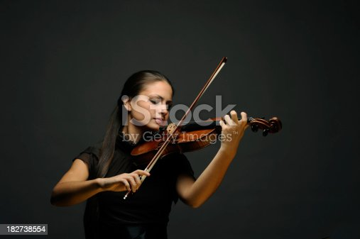 beautiful young female violinist playing violin over gray backgroundsee other similar images: