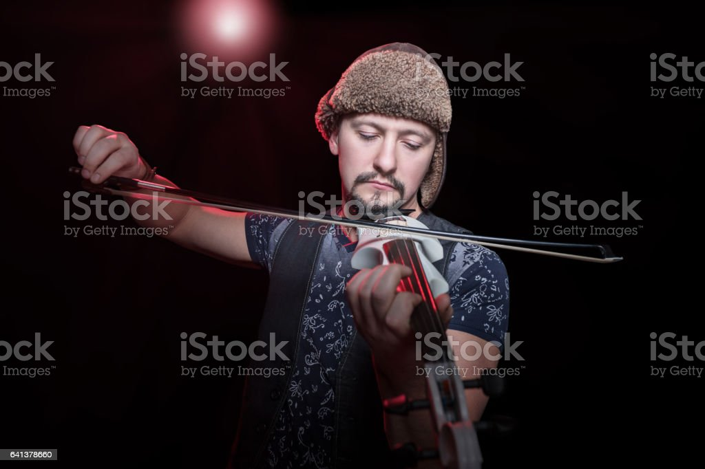 Violinist plays in concert on electroviolin stock photo