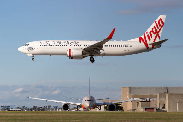 Virgin Australia Airlines Boeing 737-800 airliner about to land at Melbourne Airport while a Jetstar Airways Boeing 787 waits to depart. Melbourne, Australia - June 23, 2015: Virgin Australia Airlines Boeing 737-800 airliner about to land at Melbourne Airport while a Jetstar Airways Boeing 787 waits to depart. depart stock pictures, royalty-free photos & images