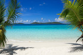 beautiful tropical beach with crystal clear water and white sand between two palm trees, St.John, US Virgin Islands