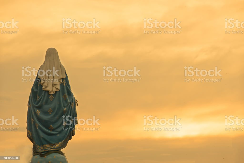 Virgin mary statue warm tone sunset scene stock photo