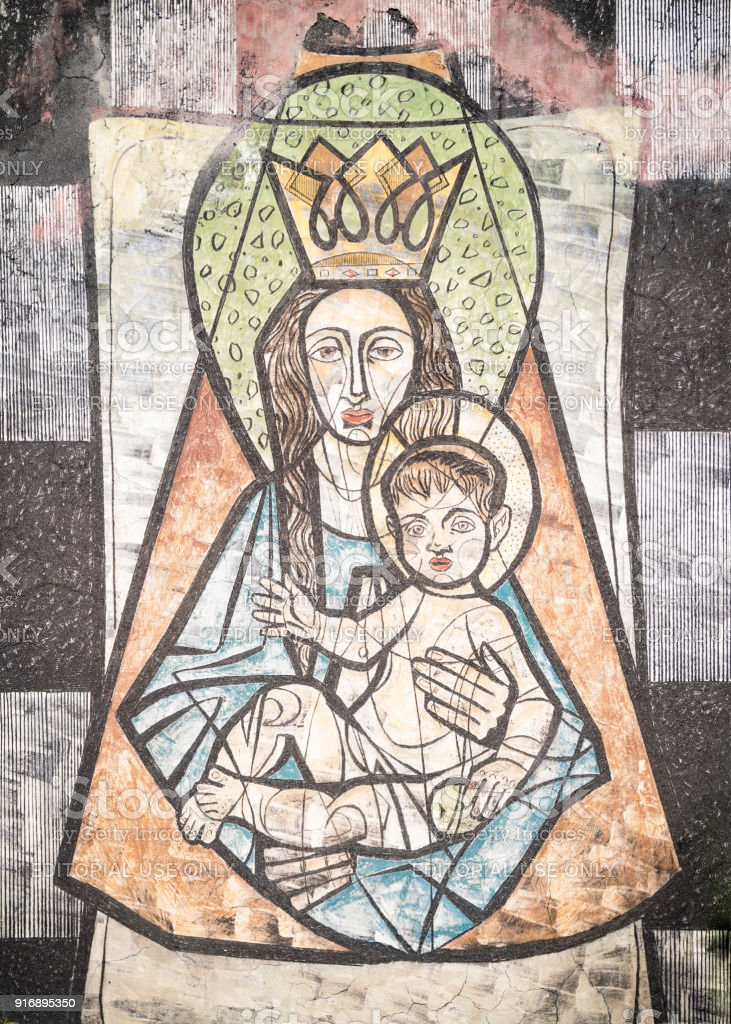 Virgin Mary with baby Jesus painted on a wall of the ancient cemetery of San Candido. stock photo