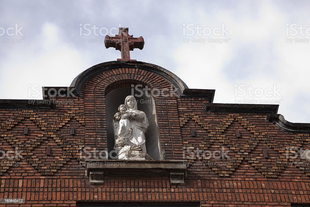 Virgin Mary with Jesus statue on old red brick school royalty-free stock photo