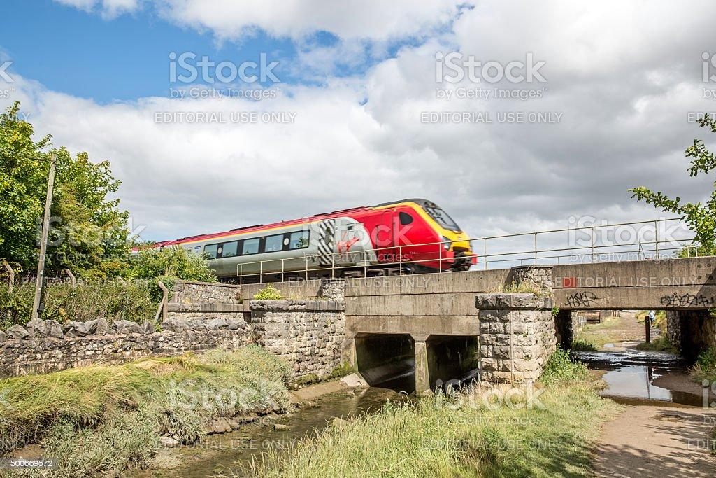 Virgin passenger train crossing river bridge stock photo