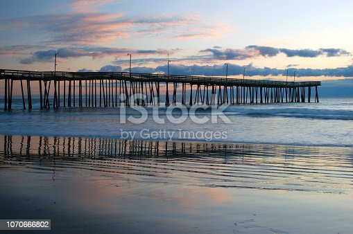 The Virginia Beach Fishing Pier is reflected in the low tide at the shore