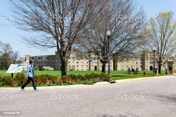 Virginia Military Institute woman walking bygreen grass lawn during sunny day in front of Clayton Hall