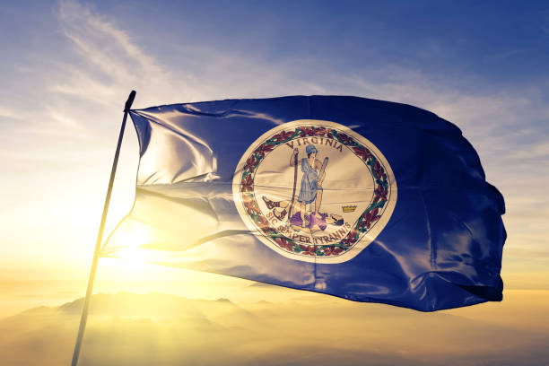 Virginia state of United States flag textile cloth fabric waving on the top sunrise mist fog stock photo