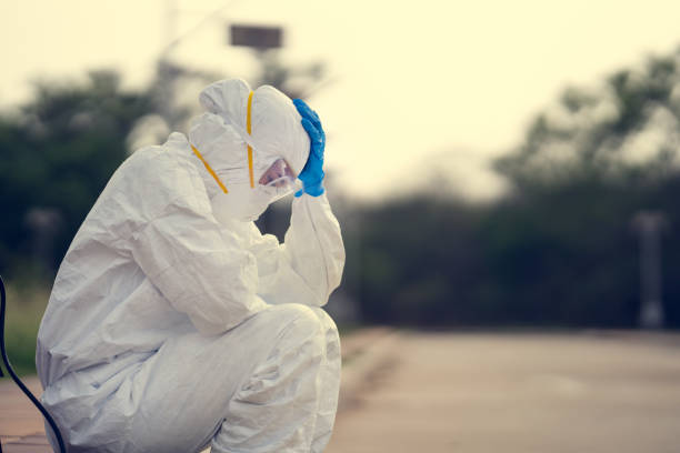Virologist, wearing PPE. She is feeling hopeless and tired. stock photo