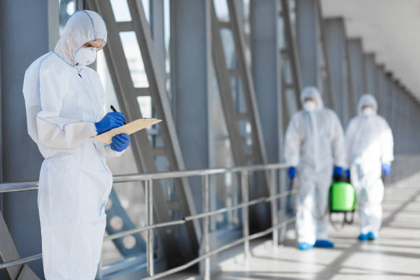Virologists in protective hazmat suits controlling epidemic stock photo