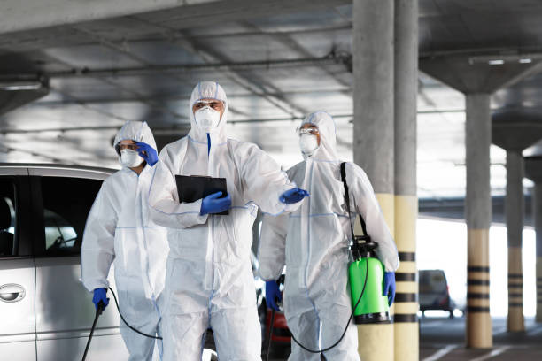 Virologists in protective suits on duty on public parking for first aid stock photo