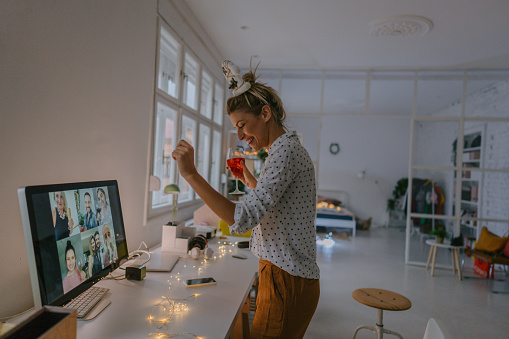 Photo of a young woman celebrating Christmas by having a virtual Christmas party with her friends; drinking wine, celebrating Christmas and holidays apart from friends and family, and practicing social distancing.