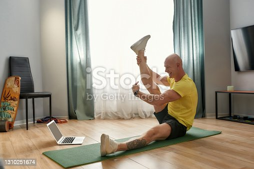 istock Virtual fitness class. Mature personal fitness conducting online training while sitting on yoga mat at home in the living room, looking at laptop and smiling 1310251674
