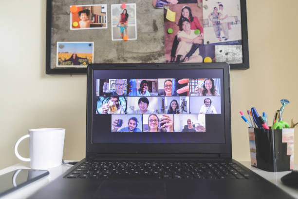Virtual happy hour with many people on screen toasting online together stock photo
