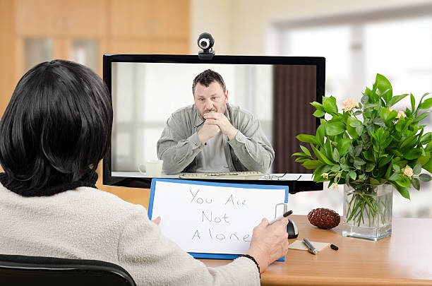 Virtual psychotherapist helps depressed man Middle aged man sitting in the monitor talks with psychotherapist via online video chat. He looking depressed. Black-haired psychiatrist holds written message for him - You are not alone. Horizontal shot indoors psychotherapy stock pictures, royalty-free photos & images