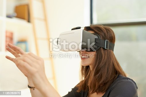 Shot of a young woman using a virtual reality headset at home
