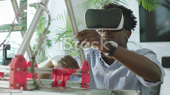 Young african ethnicity man using virtual reality headset to create device project