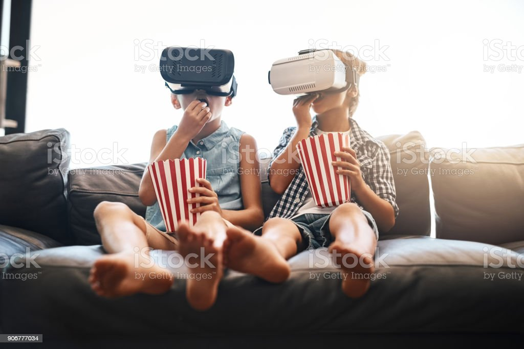 Virtual reality - not so unreal anymore Shot of a brother and sister eating popcorn and watching movies with virtual reality headsets at home Bluetooth Stock Photo