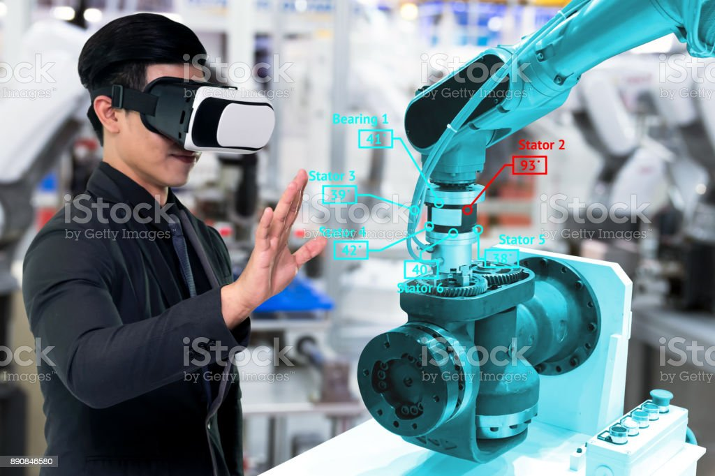 Virtual reality technology in industry 4.0. Business man suit wearing VR glasses to see AR service , Thermal Monitoring motor for check destroy part of smart robot arm machine in smart factory. stock photo