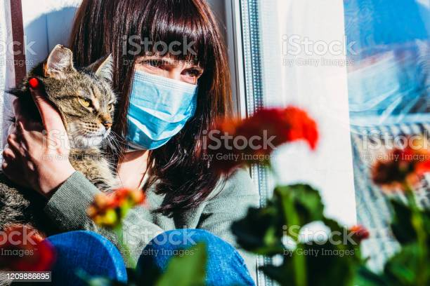 Virus a woman is sitting with a cat in a protective gauze mask from picture id1209886695?b=1&k=6&m=1209886695&s=612x612&h=fmc4xzozbkmamryzq3clh0oterpc0kbzt1bcdp 6yxy=