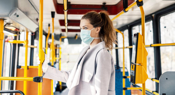 Virus protection in public transportation Woman wearing surgical protective mask going to work commercial land vehicle stock pictures, royalty-free photos & images