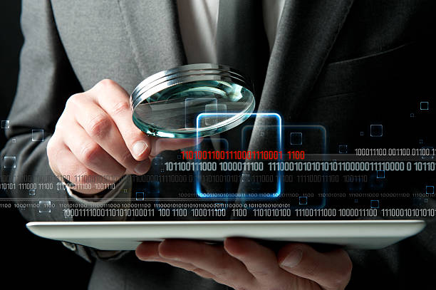 Virus search Businessman looks for the malicious code of a virus detective stock pictures, royalty-free photos & images