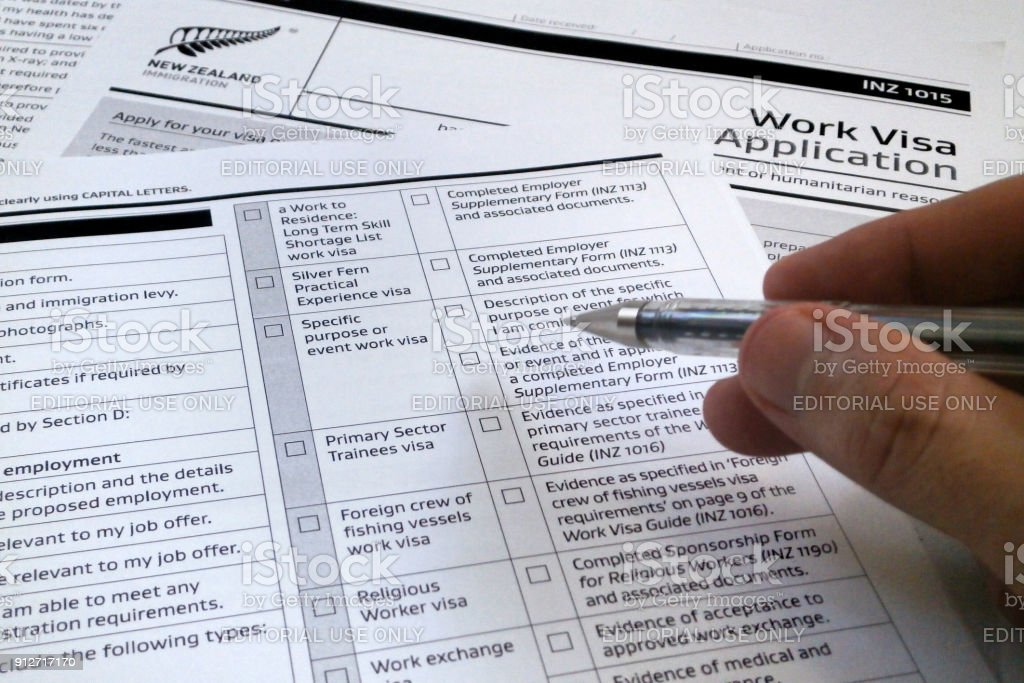 Visa application to work to New Zealand Auckland, New Zealand - April 23 2017: Somebody filling a work visa application form to work in New Zealand. Application Form Stock Photo