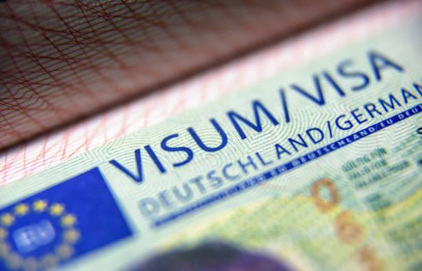 Visa stamp in passport close-up. German visitor visa at border control. Macro view of Schengen visa for tourism and travel in EU. stock photo