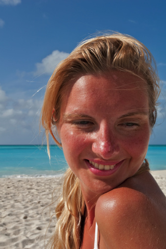 Visage of beautiful shyly smiling woman on the beach