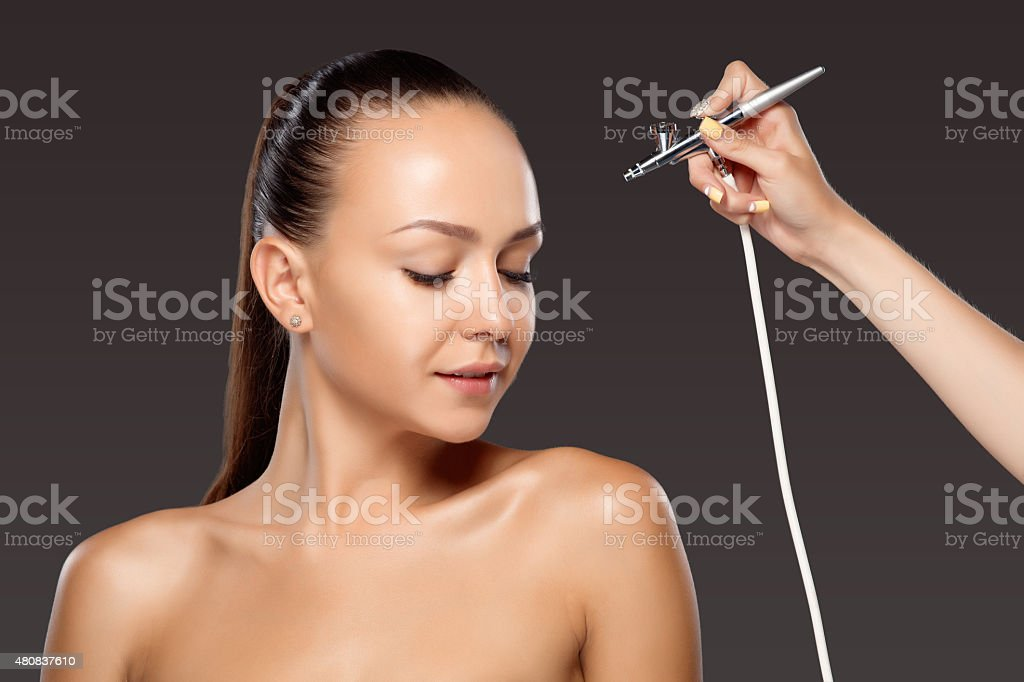 visagist making makeup for model with aerograph stock photo