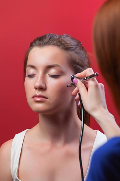 professional surfer macht make-up-modell mit aerograph für - airbrush make up stock-fotos und bilder