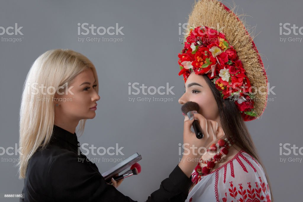 Visagiste doing makeup to the model stock photo