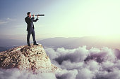 Side view of young businessman using telescope on cliff. Vision and challenge concept