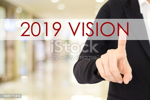 istock 2019 vision banner, Businessman hand touching 2019 vision word over blur background, annual business plan, success in business concept 1005771410