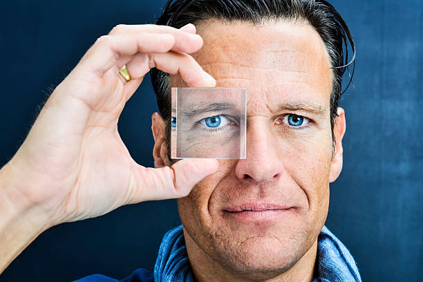 vision: man looking through lens - lens eye stock pictures, royalty-free photos & images
